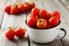 Fresh cherry tomatoes in cup on a grey wooden background Stock Photos