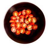Fresh cherry tomatoes cut in a half in black bowl plate isolated Royalty Free Stock Photography
