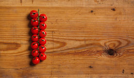 Fresh cherry tomatoes on a decorative board. The branch of cherry tomatoes on a decorative board stock images