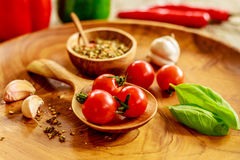 Fresh cherry tomatoes, garlic, basil leaves, mix of dry spices in wooden pot with wooden spoon on wooden tray over wooden table, r royalty free stock image