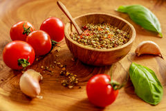 Fresh cherry tomatoes, garlic cloves, basil leaves, mix of dry spices and salt in a wooden pot with wooden spoon on wooden tray Royalty Free Stock Images