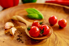 Fresh cherry tomatoes, garlic cloves, basil leaves, mix of dry spices on wooden tray Royalty Free Stock Photos