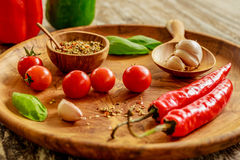Fresh cherry tomatoes, garlic cloves, chili peppers, basil leaves, mix of dry spices in wooden pot with spoon on wooden tray Stock Photography