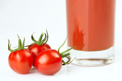 Fresh cherry tomatoes and a glass full of tomato juice.  stock photo