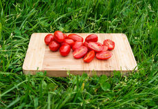 Fresh cherry tomatoes on the old wooden cutting board, closeup food, outdoors shot. Stock Image