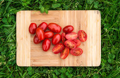 Fresh cherry tomatoes on the old wooden cutting board, closeup food, outdoors shot. Royalty Free Stock Photo