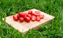 Fresh cherry tomatoes on the old wooden cutting board, closeup food, outdoors shot. Stock Photos