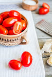 Fresh cherry tomatoes in pottery on a wooden table, close up Stock Image