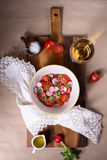 Fresh cherry tomatoes and radishes salad with wine. Bowl of fresh Mediterranean salad. Top view. Stock Images