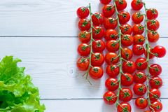 Fresh cherry tomatoes at the right part of the wooden table and green salad at the left corner stock photos