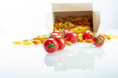 Tomatoes between colored pasta on white reflexive glass stock image