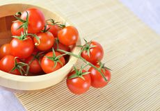 Fresh cherry tomatoes on the vine in a wooden plate Stock Photography