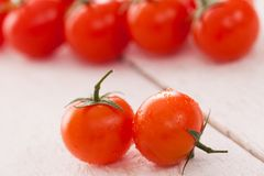 Fresh cherry tomatoes on a white surface Royalty Free Stock Photography