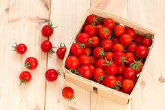 Fresh cherry tomatoes in the wooden box. On the table Stock Images