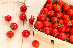 Fresh cherry tomatoes in the wooden box. On the table Stock Image