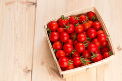 Fresh cherry tomatoes in the wooden box. On the table Royalty Free Stock Photo