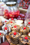 Fresh cherry-topped cupcakes and other snacks Stock Images