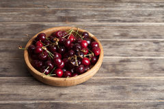 Fresh cherry in a wooden plate on an old wooden background. New harvest. Gardening. Ingredient for cooking and vegetarian food. Stock Images