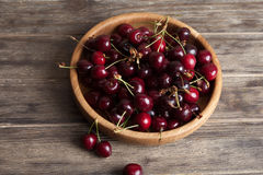 Fresh cherry in a wooden plate on an old wooden background. New harvest. Gardening. Ingredient for cooking and vegetarian food. Stock Photo