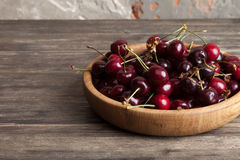 Fresh cherry in a wooden plate on an old wooden background. New harvest. Gardening. Ingredient for cooking and vegetarian food. Stock Image