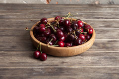 Fresh cherry in a wooden plate on an old wooden background. New harvest. Gardening. Ingredient for cooking and vegetarian food. Royalty Free Stock Photo