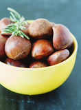 Fresh chestnuts in yellow bowl Stock Photos
