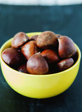 Fresh chestnuts in yellow bowl Stock Image