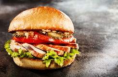 Fresh chicken breast burger on a toasted bun. With lettuce, tomato and pickled cucumber over a slate background with copy space for advertising or a menu royalty free stock images