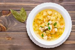 Fresh chicken broth soup with potatoes and herbs in a white bowl and bay leaf.on a wooden table stock image