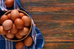 Fresh chicken brown eggs on rustic wood copy space. Bowl of organic cooking ingredients, top view. Rural still life, natural healthy food and organic farming Stock Photography