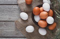 Fresh chicken brown eggs on sack, organic farming background. Poultry farm concept. Bowl with fresh brown and white eggs on burlap textile at rustic wood Stock Image