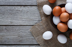 Fresh chicken brown eggs on sack, organic farming background. Poultry farm concept. Bowl with fresh brown and white eggs on burlap textile at rustic wood Royalty Free Stock Photography