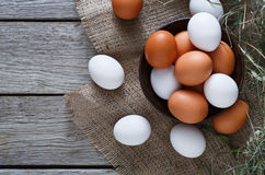 Fresh chicken brown eggs on sack, organic farming background. Poultry farm concept. Bowl with fresh brown and white eggs on burlap textile at rustic wood Stock Photos
