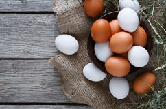 Fresh chicken brown eggs on sack, organic farming background. Poultry farm concept. Bowl with fresh brown and white eggs on burlap textile at rustic wood Stock Photo