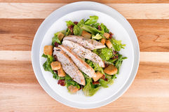 Fresh chicken caesar salad. On wooden table. View from above Stock Images