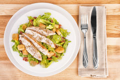 Fresh chicken caesar salad. On wooden table. View from above Stock Photo