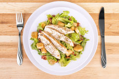 Fresh chicken caesar salad. On wooden table. View from above Stock Photos