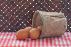 Fresh chicken eggs in bag on red tablecloth and bamboo weave bac Royalty Free Stock Images