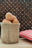 Fresh chicken eggs in bag on wooden table and bamboo weave backg Stock Photography