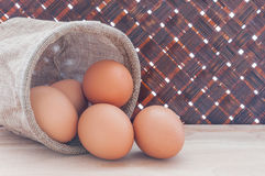 Fresh chicken eggs in bag on wooden table and bamboo weave backg Royalty Free Stock Image