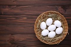 Fresh Chicken eggs in basket on brown wooden background stock photos