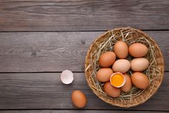 Fresh Chicken eggs in basket on grey wooden background royalty free stock images