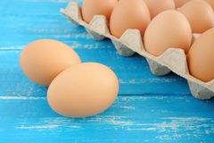 Fresh chicken eggs on blue distressed wooden table. royalty free stock photo