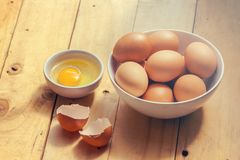 Fresh chicken eggs in a bowl on wooden table. stock photos
