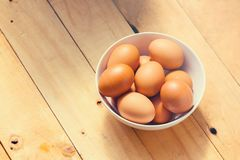 Fresh chicken eggs in a bowl on wooden table. stock photography
