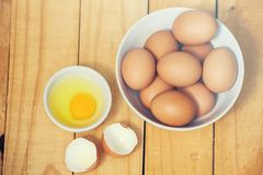 Fresh chicken eggs in a bowl on wooden table. stock photo