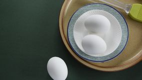 Fresh chicken eggs in ceramic  bowl with pastel colors on green background. Fresh chicken eggs in ceramic  bowl with pastel colors on deep green background stock video