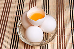 Fresh chicken eggs in a glass dish with a broken egg. On a bamboo mat Royalty Free Stock Images