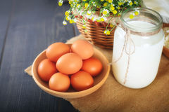 Fresh chicken eggs and a jar with milk on the kitchen table. Still life with farm products Stock Photo