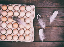Fresh chicken eggs. In a paper tray on a wooden surface, next to chicken feathers, vintage toning Royalty Free Stock Images